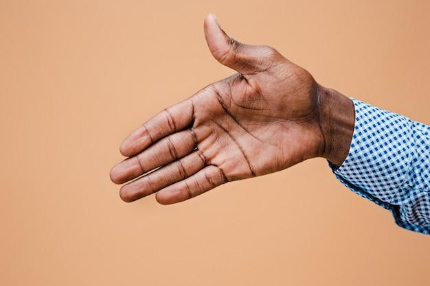 Stretta di mano. mani dell'uomo d'affari isolate su marrone