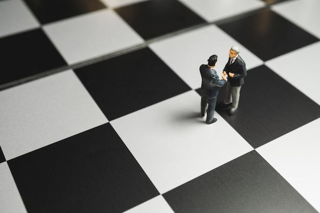 Stretta di mano miniatura dell'uomo d'affari sulla priorità bassa della scacchiera. concetto di partenariato