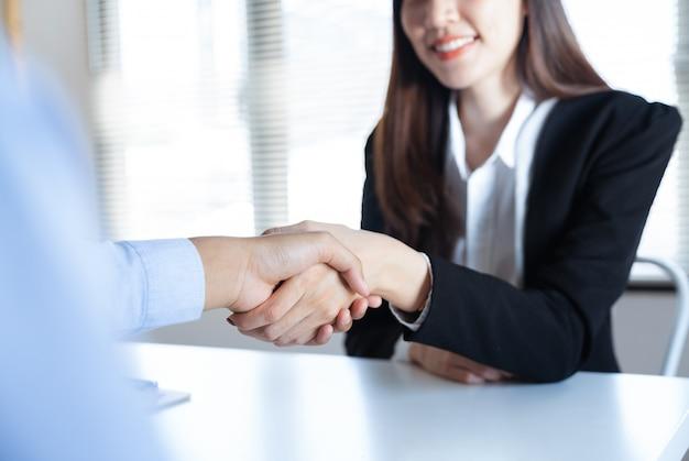 Stretta di mano sorridente della giovane donna di affari asiatica con il partner dell'uomo d'affari che fa insieme affare nell'ufficio del lavoro