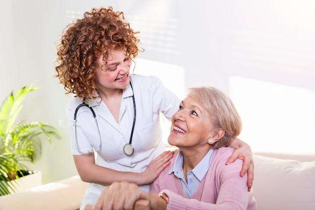 Stretta relazione positiva tra paziente anziano e caregiver. donna senior felice che parla con badante amichevole.