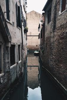 Stretto piccolo fiume in esecuzione gettare una città di periferia tra edifici in mattoni