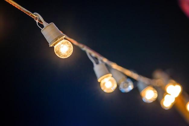 Stringa cablata con luce di riscaldamento lampadine appese nell'area degli eventi