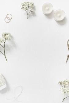 Stringhe; gypsophila; fedi nuziali; candele e scissor su sfondo bianco con copyspace per il testo