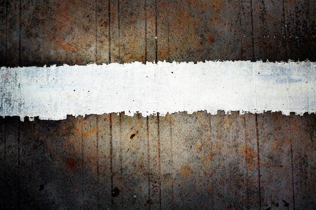 Strisce bianche sul vecchio fondo della strada cementata con colore scuro tonificato e scenetta. sfondo grunge.