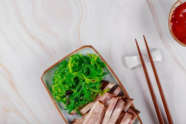 Strisce di alghe di carne alla griglia con salsa e bacchette