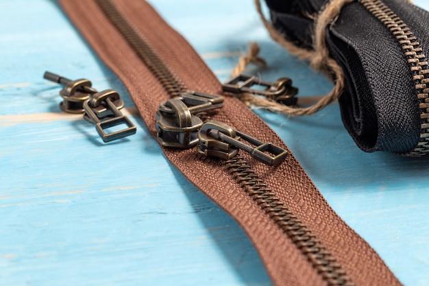 Strisce di cerniere in ottone metallo nero e marrone con cursori per fatti a mano su fondo di legno blu