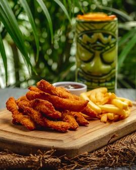 Strisce di petto di pollo impanate fritte con ketchup e patate fritte su un bordo di legno