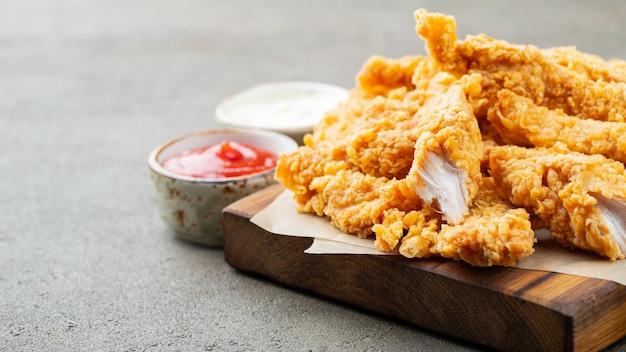 Strisce di pollo impanate con due tipi di salse.