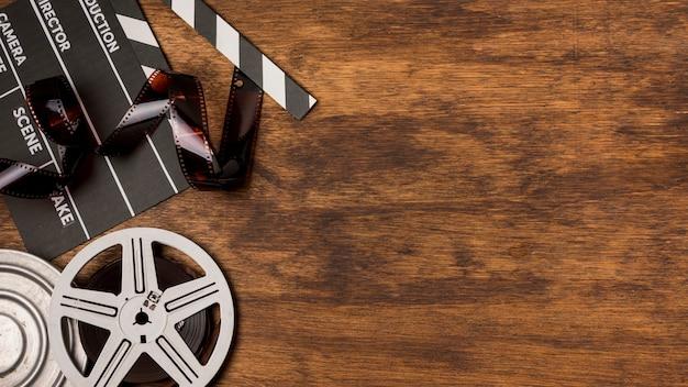 Strisce negative con ciak e bobine di film sulla scrivania in legno