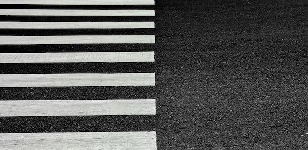 Strisce pedonali della zebra su una strada asfaltata - fondo del primo piano