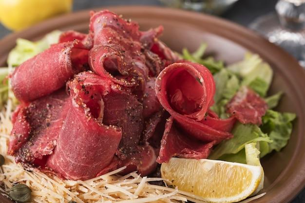 Stroganina di carne congelata cruda, capperi e limone. avvicinamento