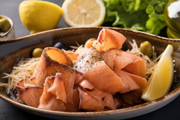Stroganina di salmone cruda congelata affettata su un piatto formaggio, olive e limone. pesce congelato a fette.