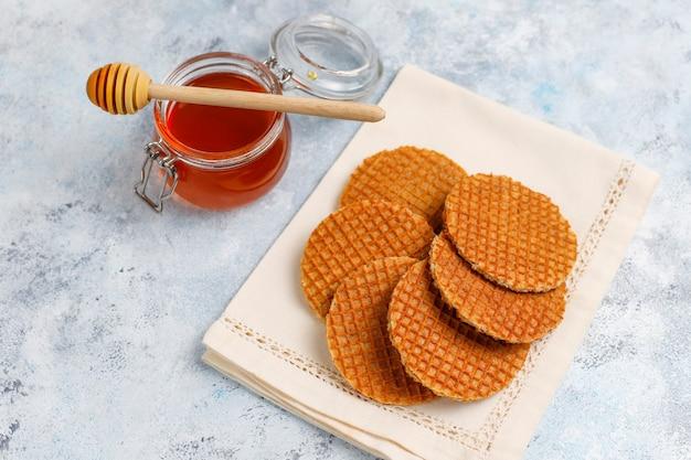 Stroopwafels, cialde al caramello olandesi con tè o caffè e miele su cemento