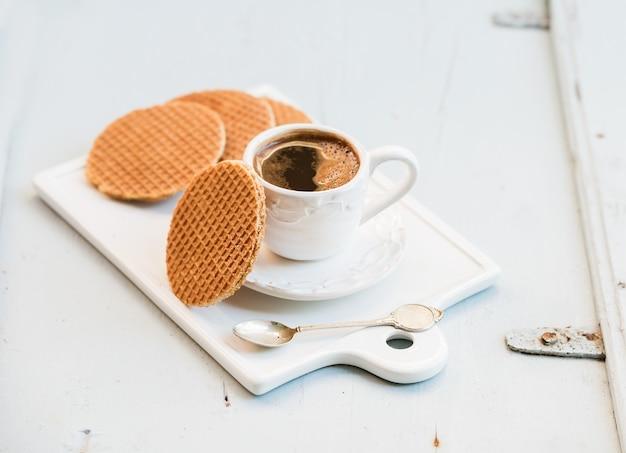 Stroopwafels e tazza di caffè neri olandesi del caramello sul bordo ceramico bianco del servizio sopra la tavola di legno blu-chiaro