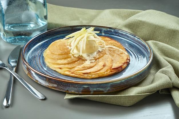 Strudel alle mele con gelato alla vaniglia su un piatto blu su una tavola di legno. popolare pasticceria e dessert austriaci. avvicinamento
