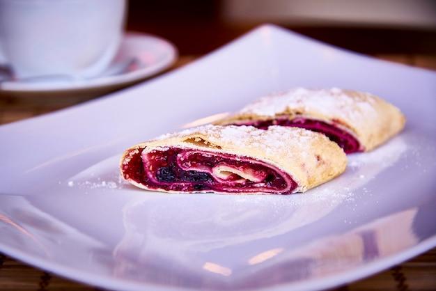 Strudel appetitoso con le bacche su un piatto bianco con polvere e una tazza su un primo piano del piattino.