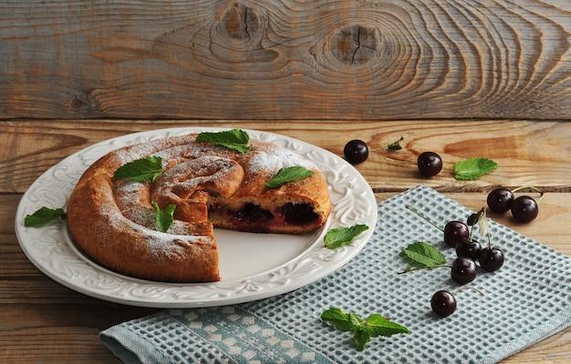 Strudel con le ciliege sul piatto su superficie di legno
