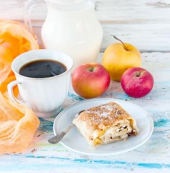 Strudel di mele, una tazza di caffè nero e brocca di latte