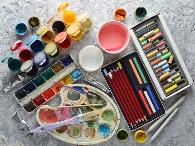 Strumenti artistici per disegnare dipinti. tavolozza, tempera, pittura ad olio, pennelli, pastelli colorati, pastelli, matite colorate. vista dall'alto.