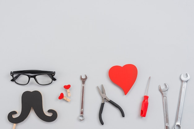 Strumenti con baffi di carta e cuore rosso