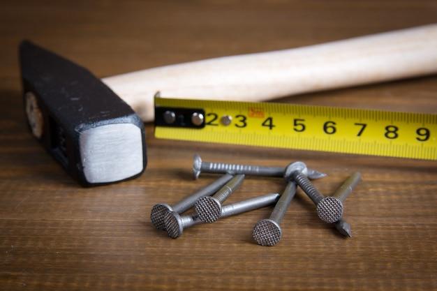 Strumenti da costruzione. martello, chiodi e nastro di misurazione su un legno.