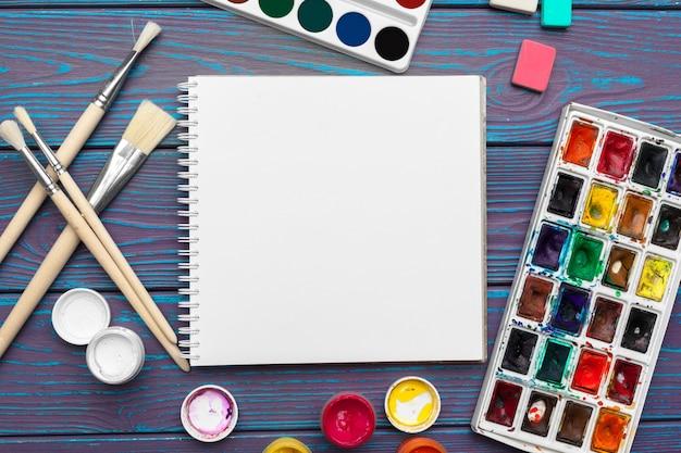 Strumenti di disegno, forniture fisse, luogo di lavoro dell'artista. vernici dell'acquerello e blocco note in bianco sullo scrittorio di legno