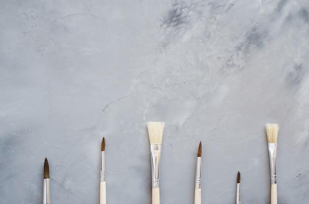 Strumenti di disegno, set di pennelli puliti su sfondo grigio.
