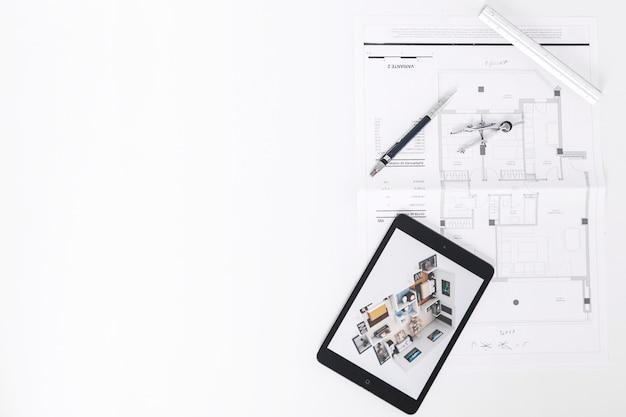 Strumenti di disegno vicino a tablet e schemi