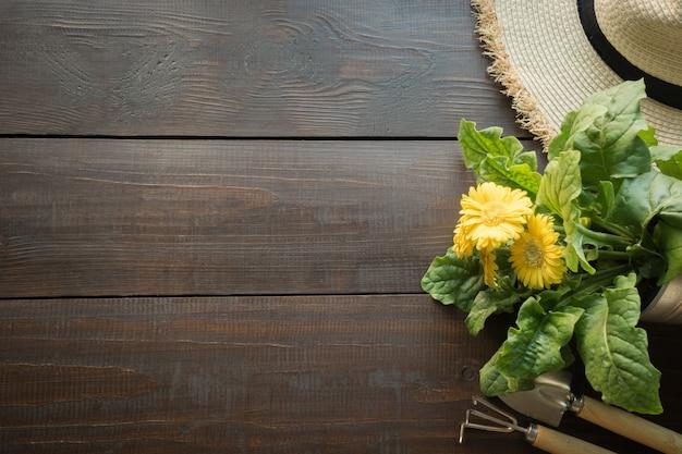 Strumenti di giardinaggio, fiori, cappello del sole della paglia e terreno sulla tavola di legno. primavera e lavoro in giardino.