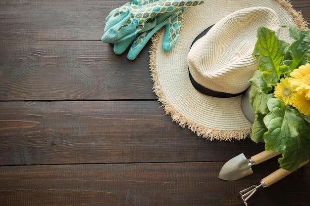 Strumenti di giardinaggio, fiori, cappello del sole sraw e suolo sulla tavola di legno. primavera e lavoro in giardino.