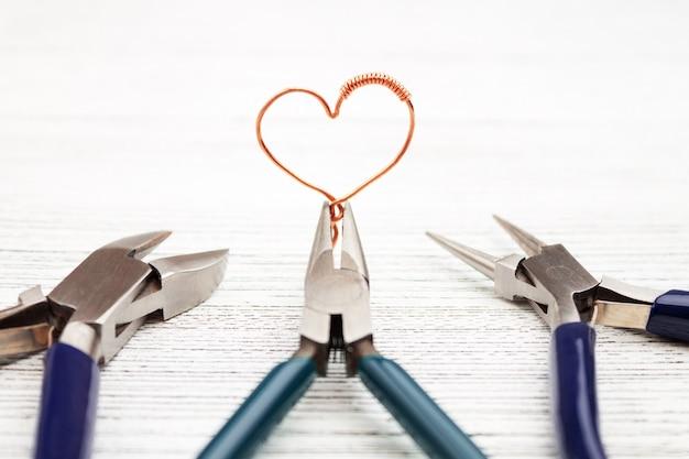 Strumenti di gioielli su bianco. cuore fatto di filo di rame. avvolgere il filo