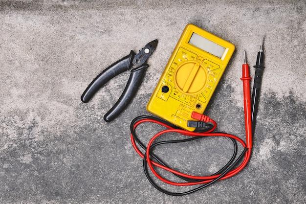 Strumenti di lavoro di elettricità domestica di diy, pinze e multimetro giallo sul fondo del cemento