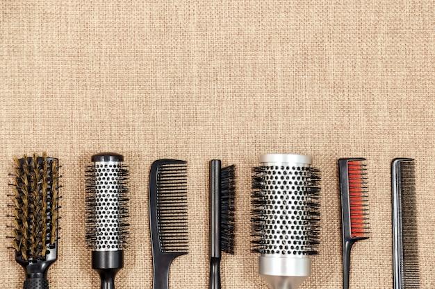 Strumenti di lavoro di parrucchiere su fondo beige con spazio in cima