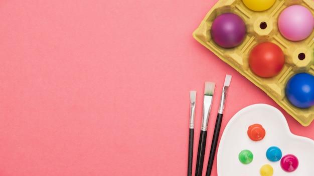 Strumenti di pittura copia-spazio e uova colorate