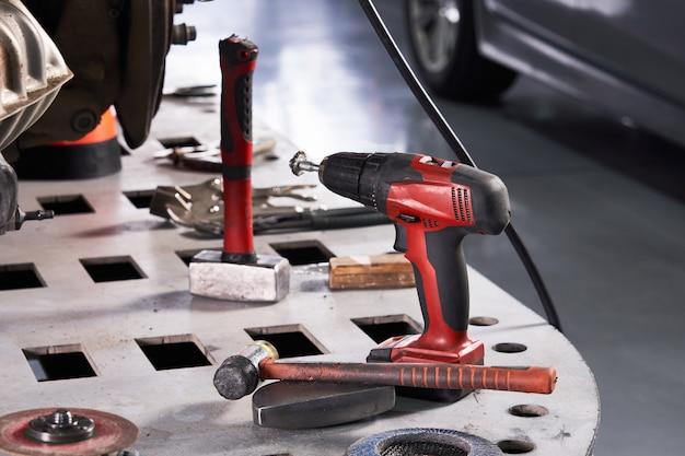 Strumenti di riparazione dell'automobile sulla tavola nell'officina riparazioni automatica