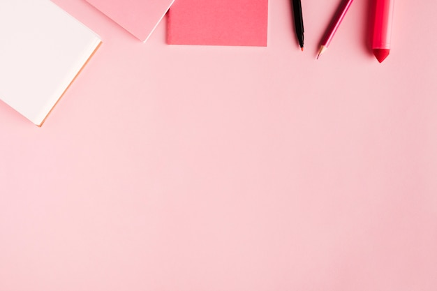 Strumenti di scuola rosa sulla superficie colorata