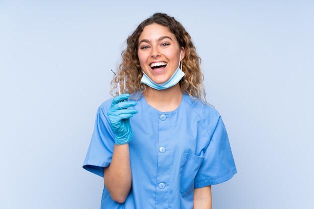 Strumenti di tenuta biondi del giovane dentista della donna sulla parete blu con espressione facciale di sorpresa