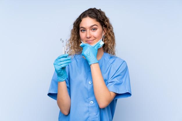 Strumenti di tenuta biondi della giovane dentista della donna sulla risata blu della parete