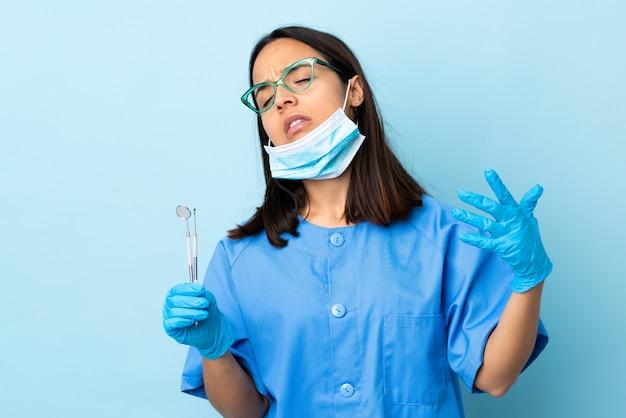Strumenti di tenuta della giovane donna castana del dentista della corsa mista sopra isolati con l'espressione stanca e malata
