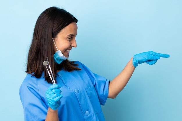 Strumenti di tenuta della giovane donna del dentista della corsa mista del brunette sopra priorità bassa isolata che indica barretta il lato e che presenta un prodotto
