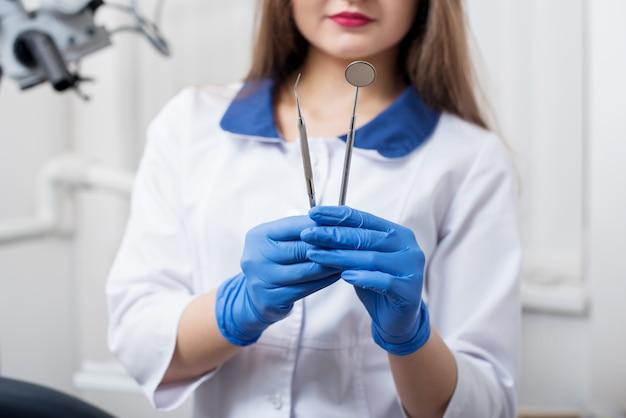 Strumenti di tenuta femminili del dentista - specchio dentale e sonda dentale all'ufficio dentale