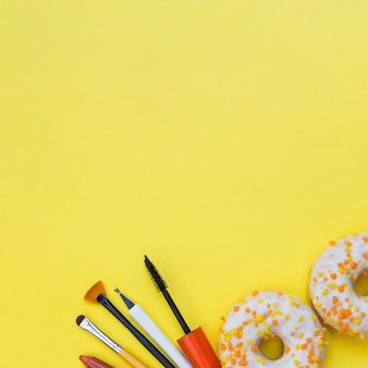 Strumenti di trucco e due ciambella su sfondo giallo