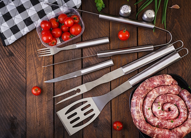 Strumenti e salsiccia del barbecue sulla tavola di legno. vista piana, vista dall'alto