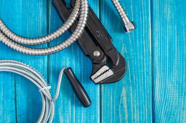Strumenti e tubo flessibile per idraulico maestro su tavole di legno blu vintage, piatto lay