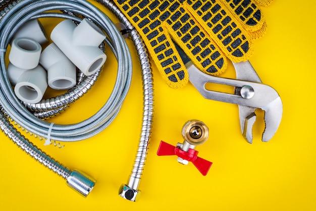 Strumenti idraulici e guanti per il collegamento di tubi dell'acqua