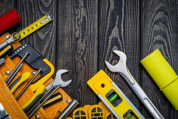 Strumenti nella borsa per carpenteria e accessori su assi di legno neri