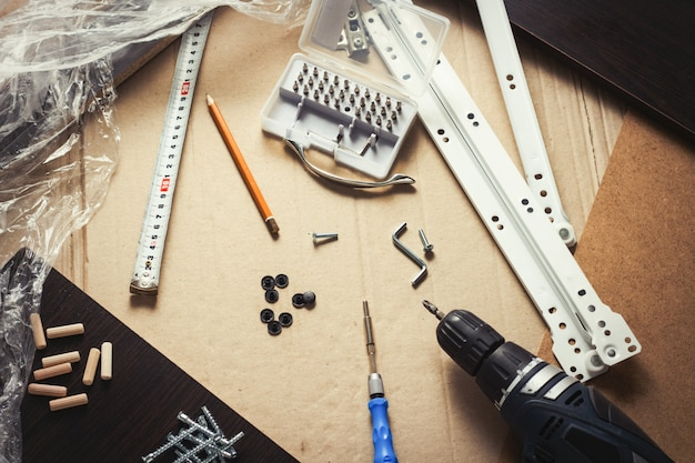 Strumenti, parti di mobili, pellicola per avvolgimento, viti su un foglio di cartone. costruire mobili manualmente. concept workshop. vista piana, vista dall'alto