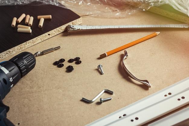 Strumenti, parti di mobili, pellicola per avvolgimento, viti su un foglio di cartone. costruzione manuale di mobili, mobili autoassemblanti