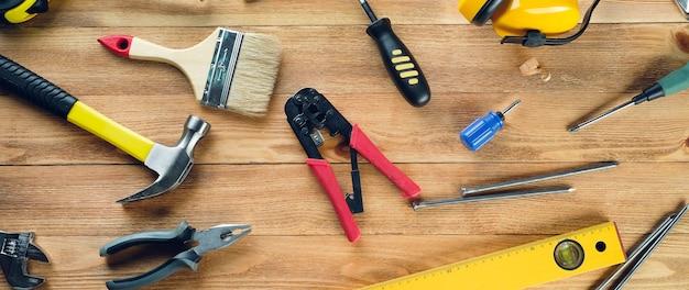 Strumenti per costruire una casa o riparare un appartamento, su un tavolo di legno. banner.