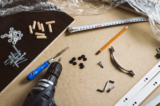 Strumenti per il montaggio di mobili, dettagli di mobili, film di avvolgimento, viti su un foglio di cartone. concept workshop